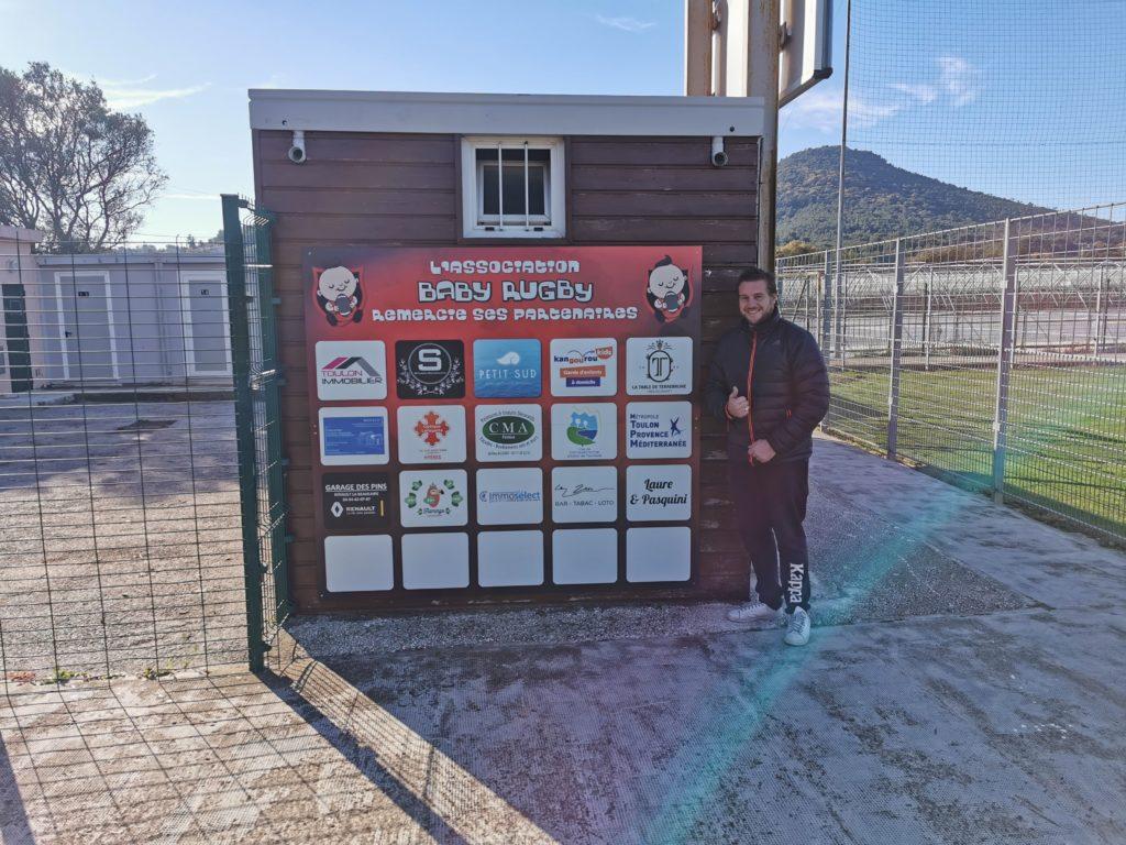 Bastien Miquelis lors de la mise en place du panneau des partenaires au stade Tassy de Carqueiranne.